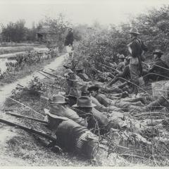 U.S. soldiers lie behind an embankment, watching the enemy, 1899