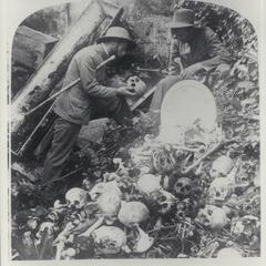 Two men examine a skull in the bone pit at Santa Cruz Cemetery, Manila, 1899