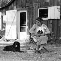 Estella Bergere Leopold seated in front of the Shack, with binoculars and dog (summer), ca. 1960