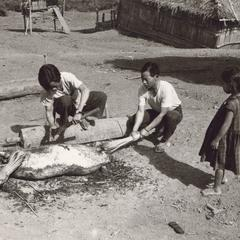 White Hmong man sharpens machete in Houa Khong Province