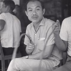 Mr. Autit is seated with villagers in Houei Kong