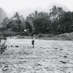 A Lao woman wades across the Nam Xong River near the town of Vang Vieng in Vientiane Province