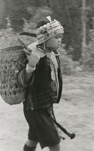 Young Akha girl carries vegetables from the family garden to the village of Phate in Houa Khong Province