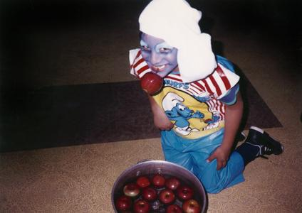 Boy in costume bobbing for apples