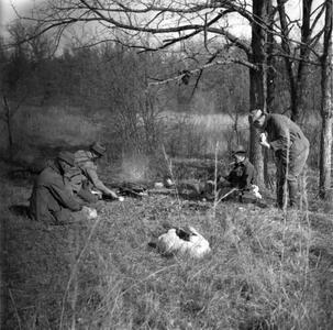 Aldo Leopold, Luna Leopold, Ray Roark, and Flick sitting at campsite