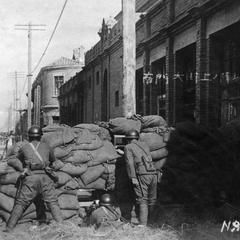 Japanese soldiers in position on the street outside the South Gate.