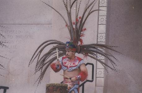 Man drumming in traditional dance costume on Library Mall