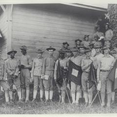 Black and white U.S. troops with signal corps flag, 1899-1902