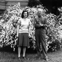 With secretary Alice Harper, 1938, in front of flowering shrub