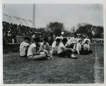 Phi Omega Beta pledges sitting on the sidelines of a football game, next to the Stout Cheerleaders
