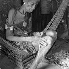Woman Rolling Rope Out of Plant Fiber to Make a Fish Trap