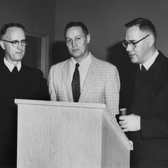 Three unidentified men standing by lectern.