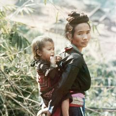 A Blue Hmong (Hmong Njua) mother carries her child on her back in Houa Khong Province