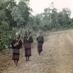 Three Nyaheun women walking on the laterite road in Attapu Province