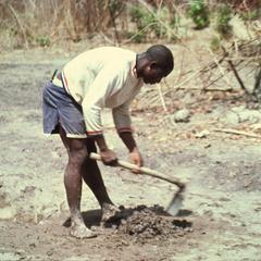 Man Mixing Mud for Bricks