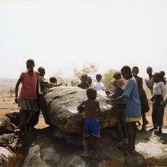 Children gathered around a large rock