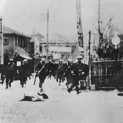 Japanese marines hurrying through a silent street.