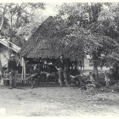 Six U.S. soldiers relax next to a thatched hut and shade trees, 1899