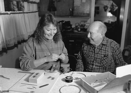Vicki Doxtator works on silver jewelry as Edwin Martin watches
