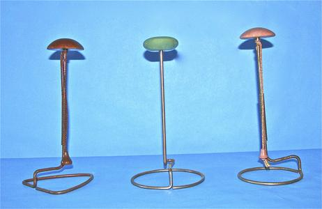 Three metal hat stands with painted tops