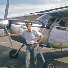 Robert Wofford standing beside a Helio Courier