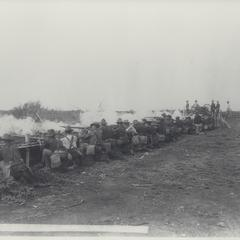U.S. soldiers fire rifles in volleys from behind a barricade, San Roque, 1899