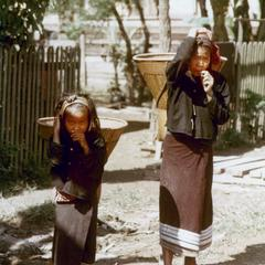 Khmu' mother and daughter carry baskets strapped to their foreheads in Houa Khong Province