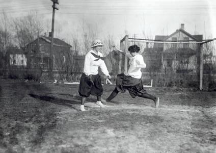 Two women play baseball