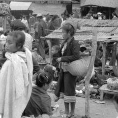 Woman with large basket (possibly Khmu', note headdress) shopping in morning market