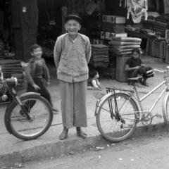 Old Chinese merchant in front of clothing shop, children in background