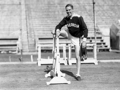 Charles McGinnis posing at a high hurdle.