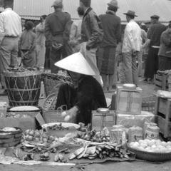 Vietnamese woman merchant selling fish on banana leaves, eggs, onions, with baskets of charcoal at her back, groups of men in background looking at merchandise