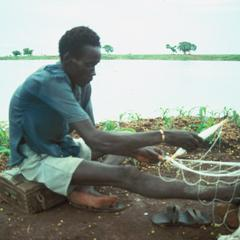 Man Preparing Fish Net by the River