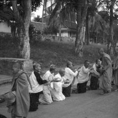 Old women with shaved heads on bended knees offering food to monks