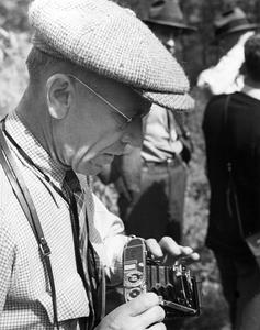 With camera, wearing tweed cap and looking down, 1935