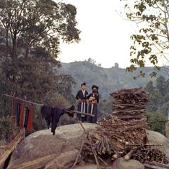 Two White Hmong women and infant stand near a pile of firewood in Houa Khong Province