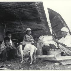 Filipino family sheltered beneath the rubble of their former home, Pasay, 1945