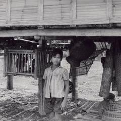 Laven boy stands under his house with fish traps in a Laven village in Attapu Province