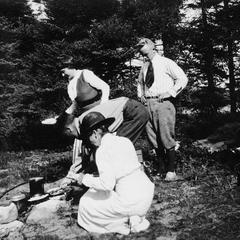 Carl Leopold Jr. and others around campfire at Les Cheneaux