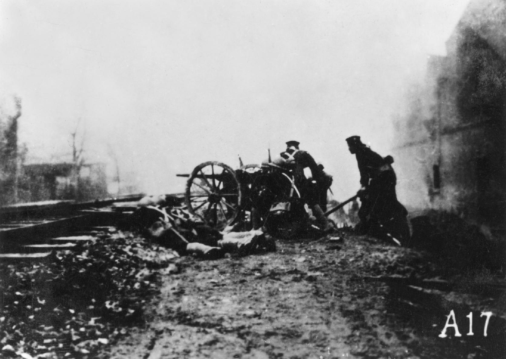 Japanese soldiers firing a light gun along a railway.