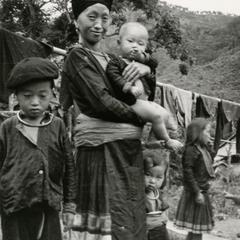 A Blue Hmong (Hmong Njua) mother with her baby and daughter and son pose in a village in the area of Vang Vieng in Vientiane Province