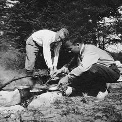 Carl Leopold Jr. and another at campfire at Les Cheneaux