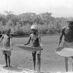 Family Winnowing Rice by the River