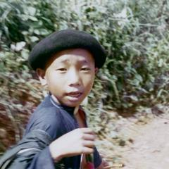 Young Akha boy walking on a path between villages in Houa Khong Province
