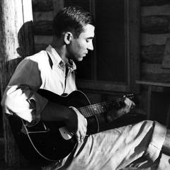 Starker Leopold with guitar at Missouri cabin