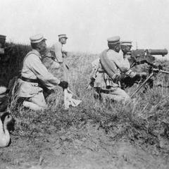 Chinese soldiers led by an officer carrying a machine gun.
