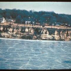 View of frozen Lake Mendota and Maple Bluff with disturbed sugar maple forest, probably early 20th century
