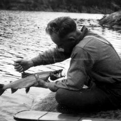 Cleaning fish at water's edge, Boundary Waters, August 1924