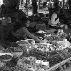 Woman selling soap powder, soap, condensed milk, bottles of sauce, dried foods at stand