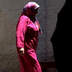 Woman Passing Market Stall in Fez Medina